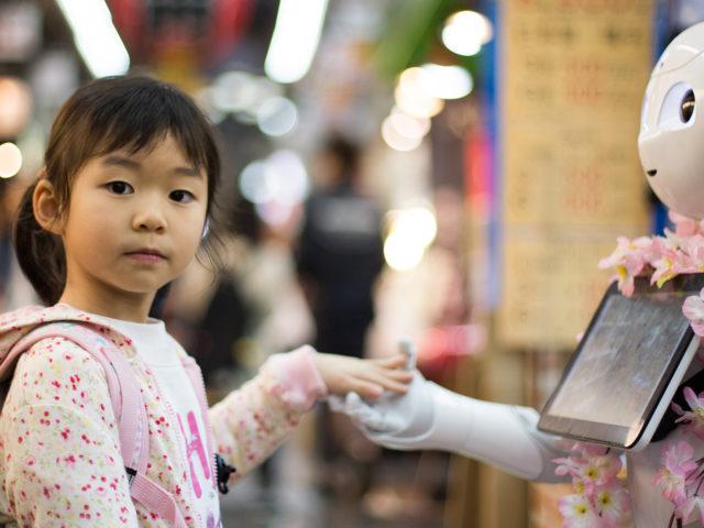 Petite fille donnant la main à un robot