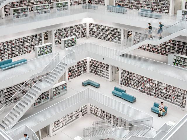 Grand escalier ouvert sur les rayonnages d'une bibliothèque entièrement blanche